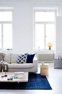 Des touches de bleu dans le tapis et les coussins du salon