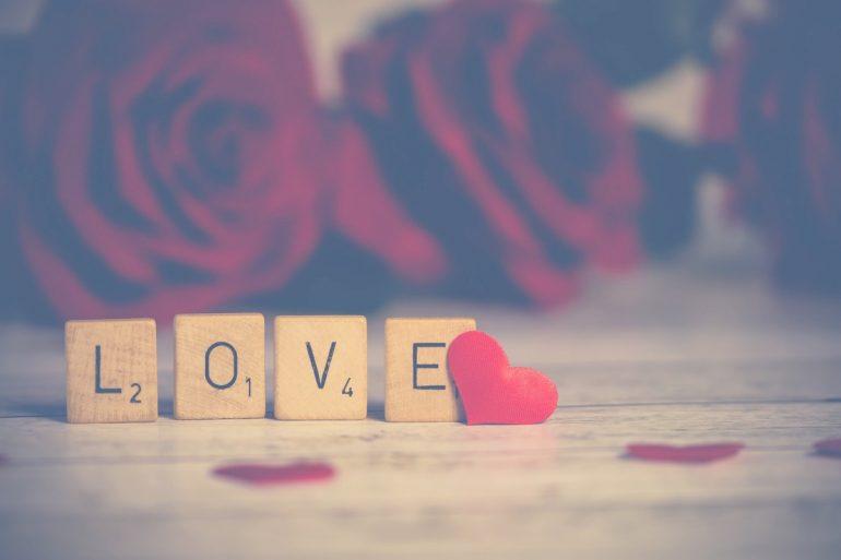 Love écrit en lettres de Scrabble avec des coeurs et des fleurs