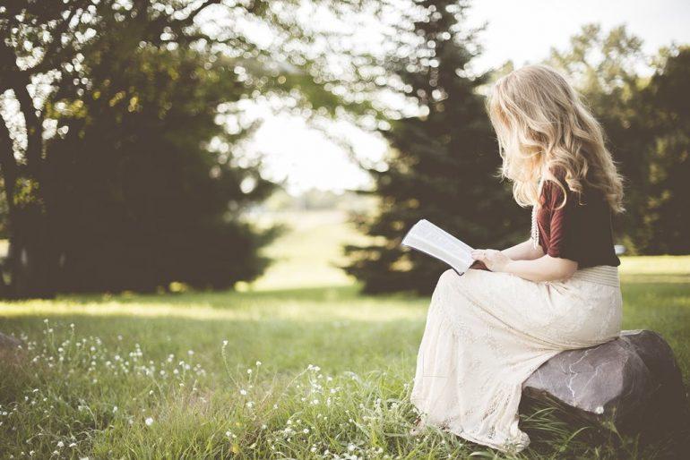 Jeune fille qui lit un livre dans un parc