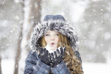 Femme qui souffle dans la neige en hiver
