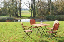 Mobilier de jardin en bois et en métal, dans un beau jardin devant une rivière