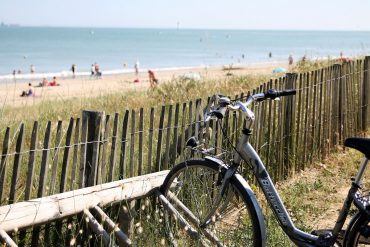 Photo d'un vélo contre les barrières donnant accès à une plage de Charente Maritime