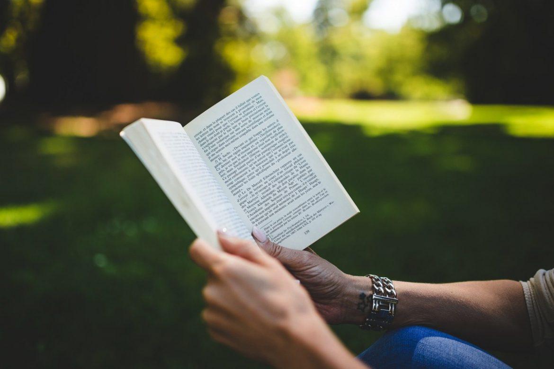 Femme qui lit un livre dans un parc
