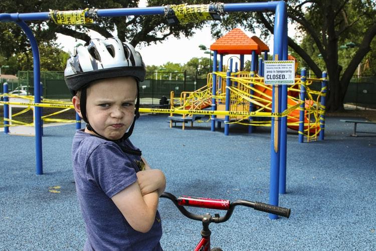 Jeune garçon qui boude sur son vélo, dans une aire de jeux pour enfants.