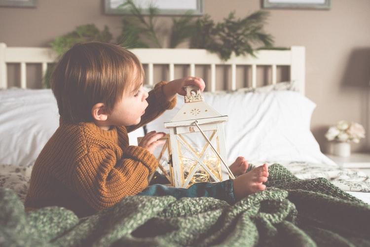 Petit garçon de 2 ans qui joue sur un lit d'adulte