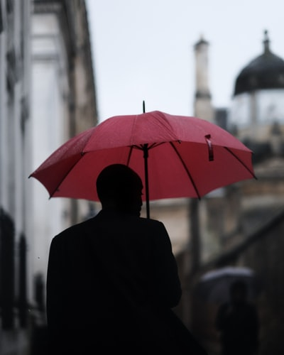 Homme sous un parapluie rouge