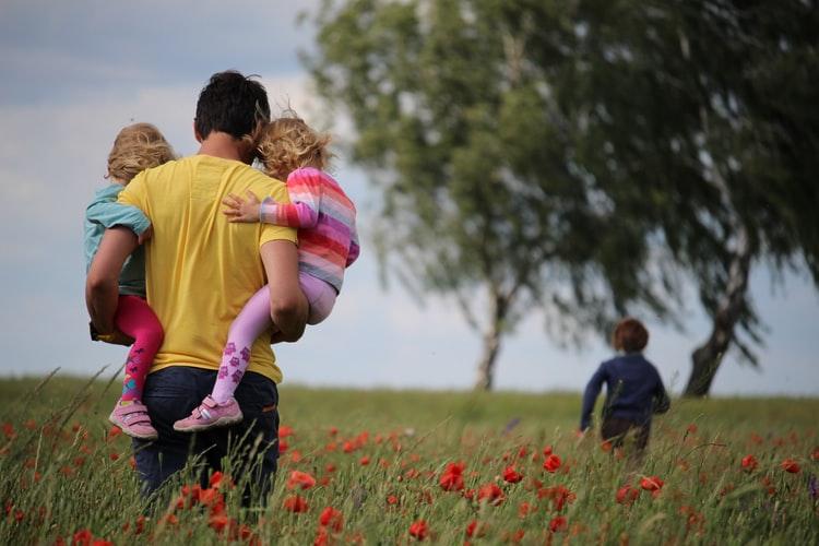 Un père avec ses trois enfants dans un champs de coquelicots.
