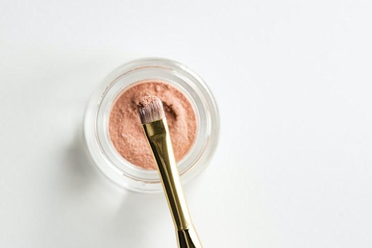 Pinceau à maquillage dans un pot de far à paupières.