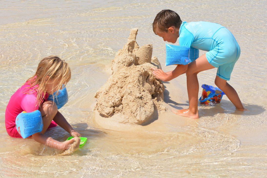 Deux enfants qui font un château de sable sur la plage