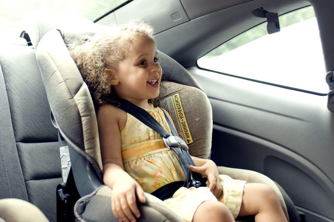 Une petite fille dans un siège auto, dans une voiture sur la route des vacances