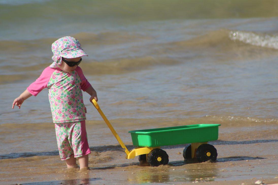 Enfant qui traine un chariot à la plage