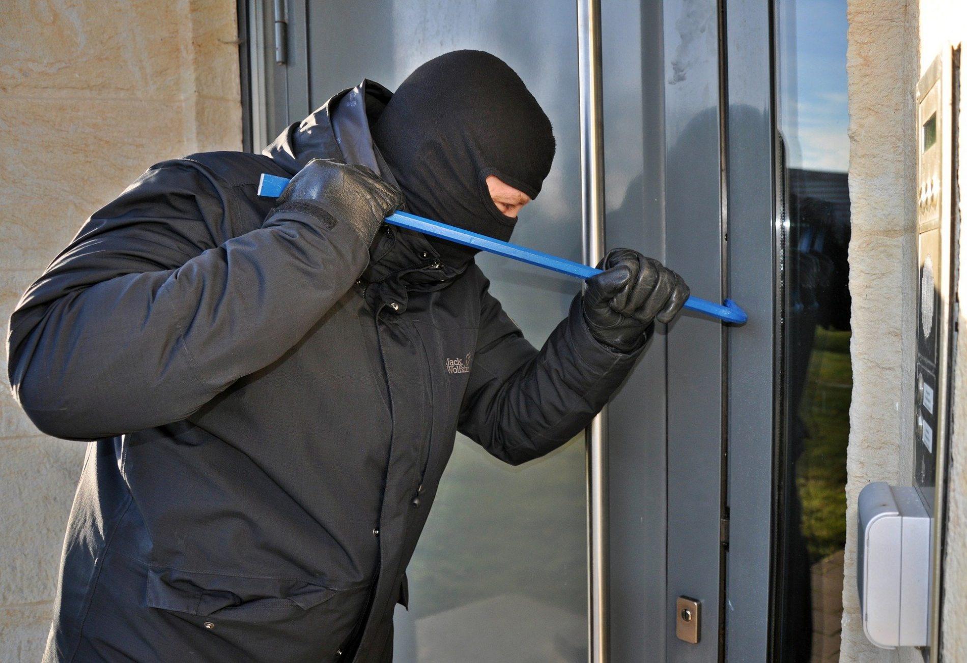Homme masqué qui essaie d'entrer dans une maison par effraction