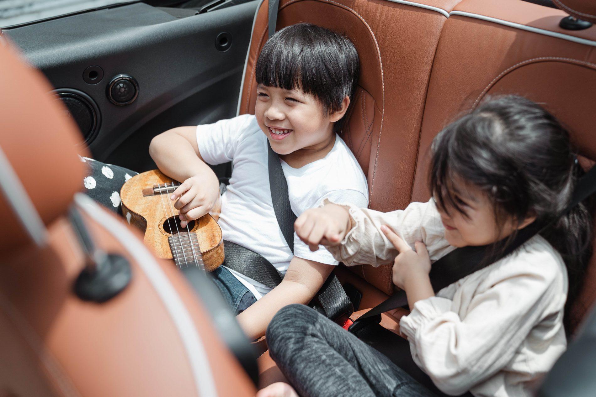 Deux enfants en train de jouer sur la banquette arrière d'une voiture, sur la route des vacances