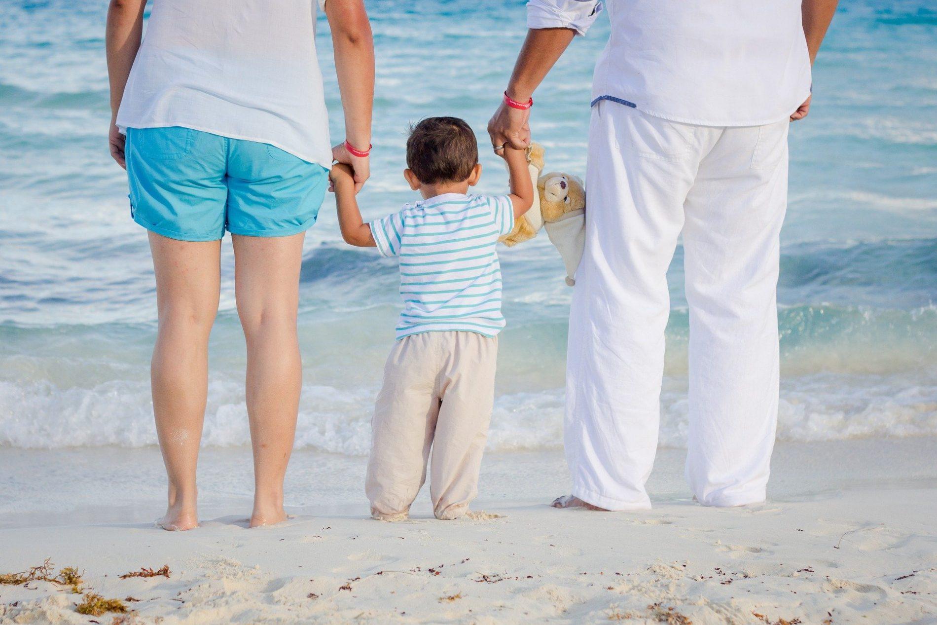 Un enfant tenant ses parents par la main au bord de la mer sur la plage.