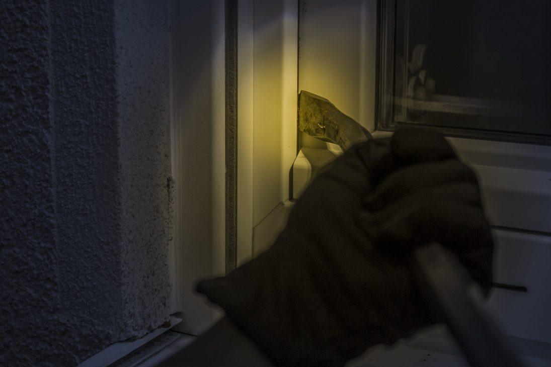 Main avec un pied de biche qui essaie de fracturer une fenêtre